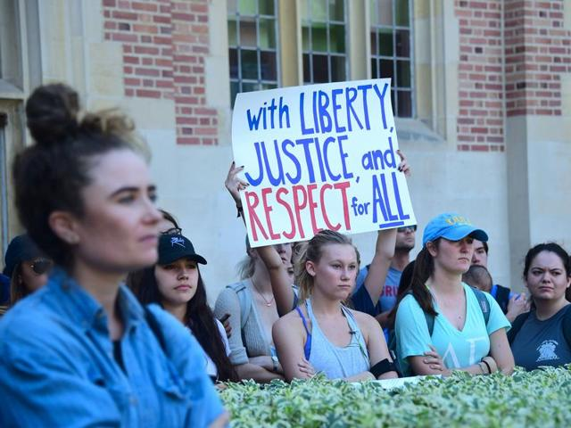 University of California Los Angeles students hold signs and listen to speeches before marching through campus on Thursday during a
