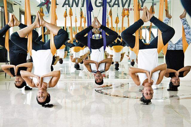 A group of women hang upside-down from hammocks during an anti-gravity suspension workout at Biorhythm Studio, Pune.