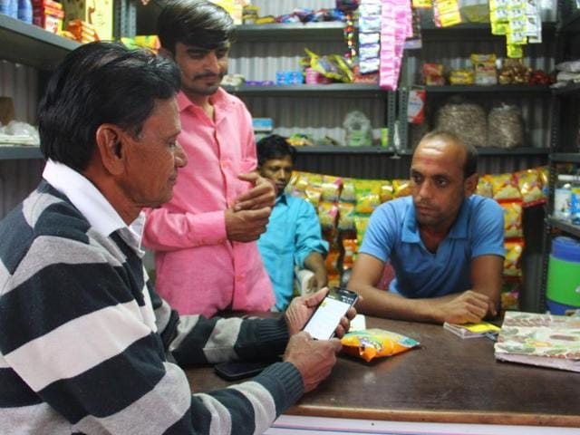 Customer Manilal Prajapati pays shop owner Pankhi Patel via SMS in Akodara, Gujarat. Akodara is India's first 'digital village' where families fall back on e-banking for everything.