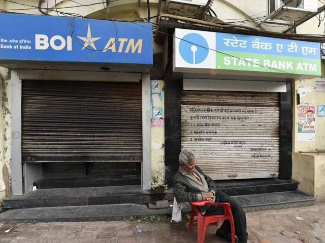 A guard takes a nap in front of closed ATMs in Lucknow on Friday.
