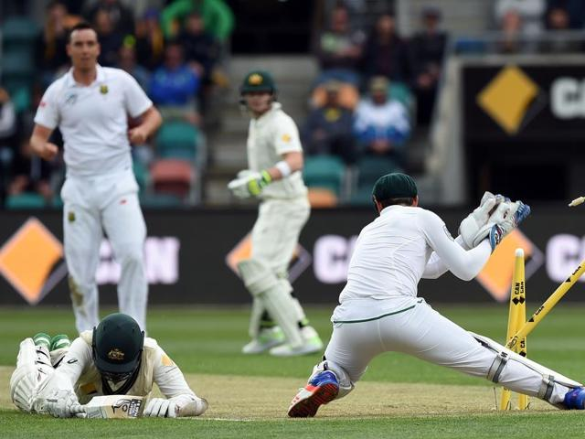 South Africa's wicketkeeper Quinton de Kock removes a stump as he tries to run out Australia's Nathan Lyon.