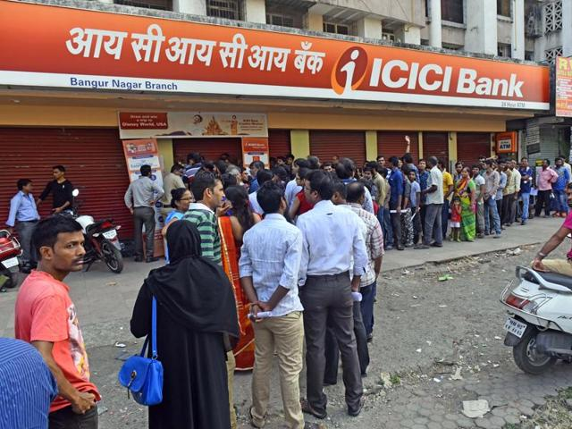 Customers line up outside an ATM on Friday.