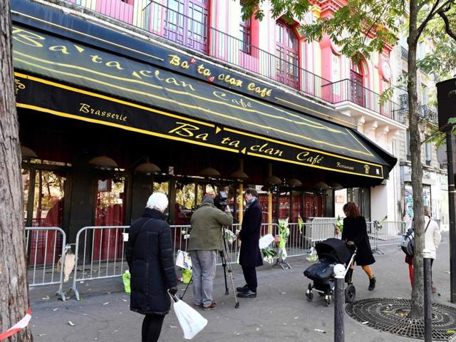 People walk in front of the Bataclan concert hall in Paris on Friday.