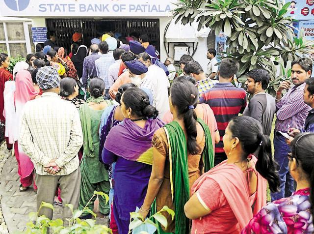 Customers standing in queues outside the State Bank of Patiala on Friday.