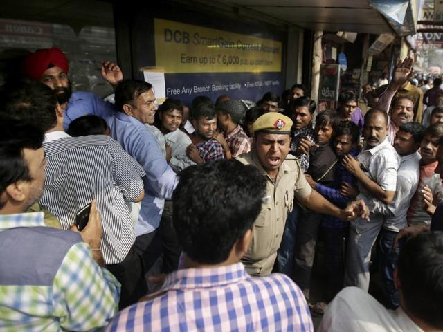 An Indian policeman shouts at people who jumped the queue outside a bank in New Delhi,  last Saturday. Long lines have grown longer, scuffles have broken out and chaotic scenes are being seen across India.