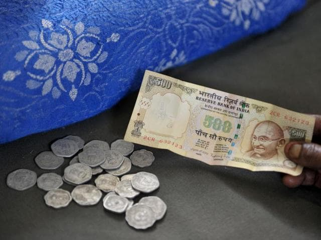 A resident hands a Rs 500 note to a money lender at his shop in Hyderabad on November 9, as he seeks to exchange it for lesser denominations.