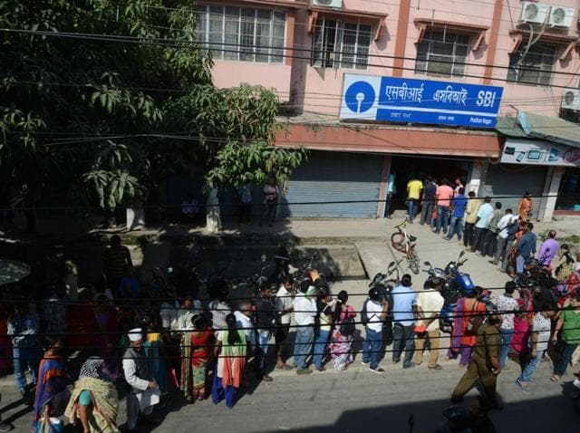 Customers waits next to a closed ATM as others queue to exchange old 500 and 1000 rupee notes and deposit money at a bank in Siliguri.(AFP Photo)
