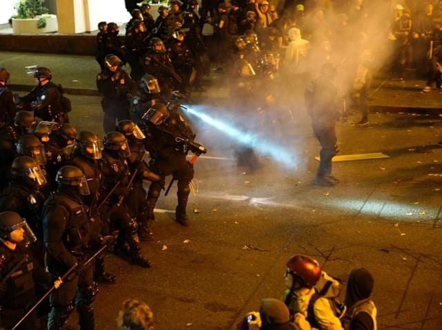 A police officer sprays the crowd with an irritant during a protest against the election of Republican Donald Trump as President of the United States in Portland, Oregon.