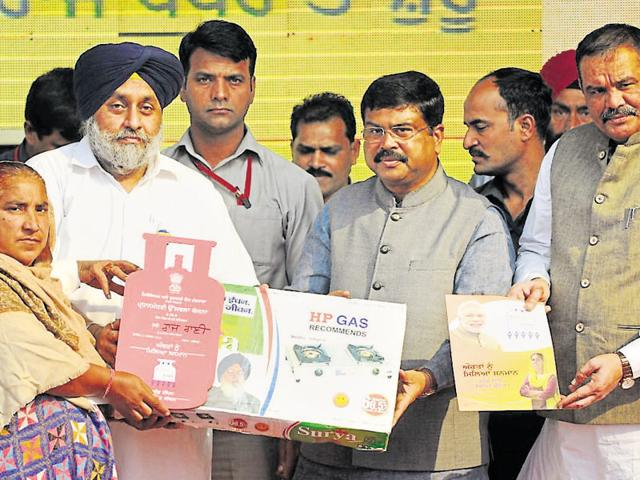 (From right) Union minister of state for social justice and woman empowerment Vijay Sampla, petrolem and natural gas minister Dharmendra Pradhan, deputy chief minister Sukhbir Badal  giving a gas connection to a woman under the Pradhan Mantri Ujjwala Yojana in Jalandhar on Friday.