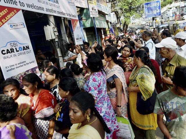 People scuffle to exchange Rs 500 and Rs 1,000 notes at a bank in Chennai on Friday.