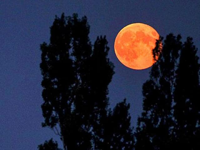A supermoon is seen on September 9, 2014 from the central French city of Luynes. A supermoon occurs when the timing of a full moon overlaps with the point in the moon's 28-day orbit that is closest to Earth.
