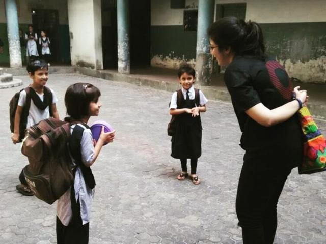 A college student  interacts with students of a civic school during the study visit. The students inspected classrooms, laboratories and toilets and, on Saturday, submitted a report of their findings to the BMC.