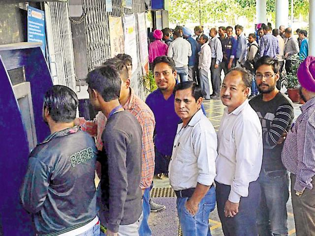 People standing in queues outside banks in Sector 17 on Saturday.
