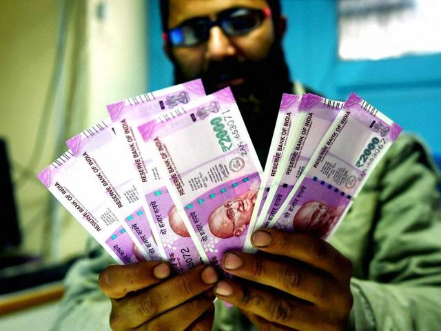A bank employee counting new Rs 2000 notes before issuing to the customers in Srinagar on Thursday.