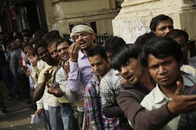 A man gestures to convey that he has no money to buy food, as he stands in a queue with others to deposit and exchange discontinued currency notes outside a bank in New Delhi.
