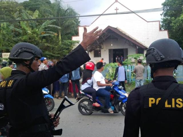 Two Indonesian policemen stand guard outside the Oikume church after a man allegedly threw molotov cocktails into the church compounds in Samarinda, East Kalimantan.