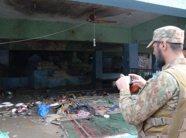 A Pakistani army soldier takes picture of suicide blast site in a shrine of Sufi saint Shah Noorani, some 750 kilometres south of Quetta.