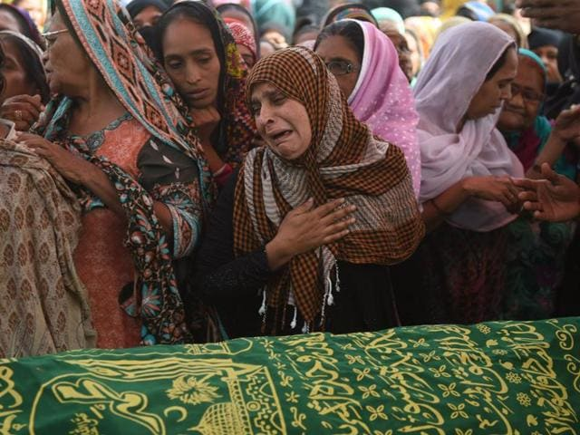 Pakistani mourners surround the coffin of a relative killed in a bomb attack on the Shah Noorani Sufi shrine ahead of his funeral in Karachi on November 13, 2016. At least 52 people died and more than 100 others were injured November 12 in a bomb blast at a remote Sufi shrine in Pakistan, officials said, with the Islamic State group claiming the attack.