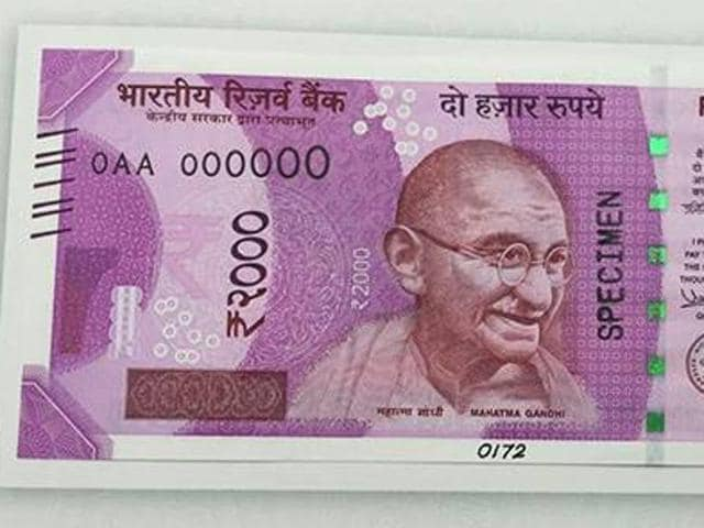 Police with the two men accused (faces covered) of printing counterfeit notes of Rs 2,000 at Bhikhiwind in Tarn Taran district on Monday.