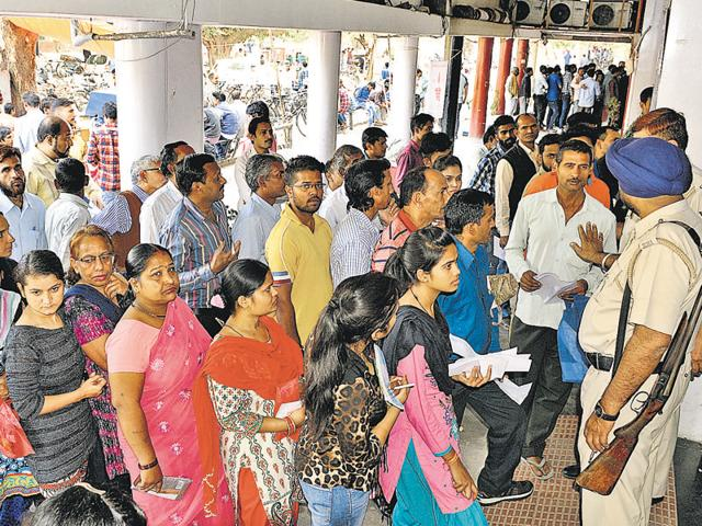 People queue up outside a State Bank of India branch in Sector 30, Chandigarh, on Sunday