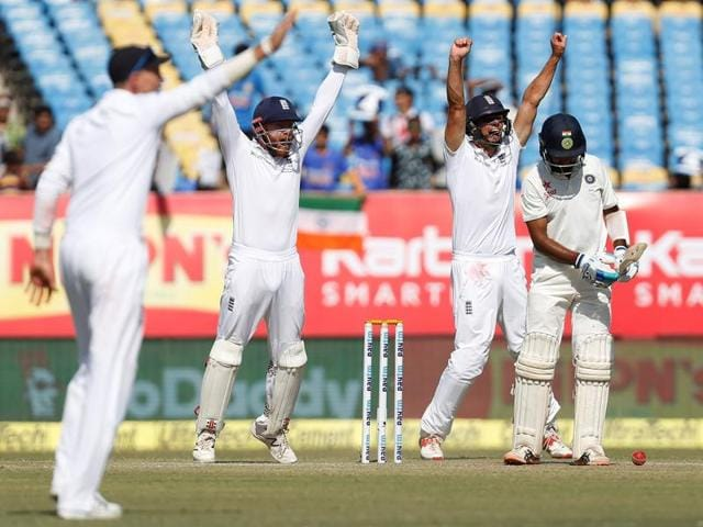 England's players successfully appeals for India's Cheteshwar Pujara's (R) dismissal.