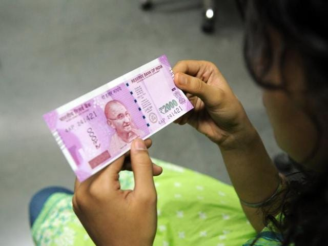A boy shows a new 2000 Indian rupee note which he got in exchange. People have complained of being duped by colour copies of the new Rs 2000 currency.