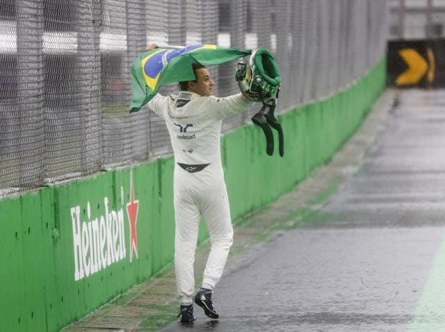 Felipe Massa of Brazil wears his country's flag over his shoulders as he celebrates with fans at Brazilian GP.