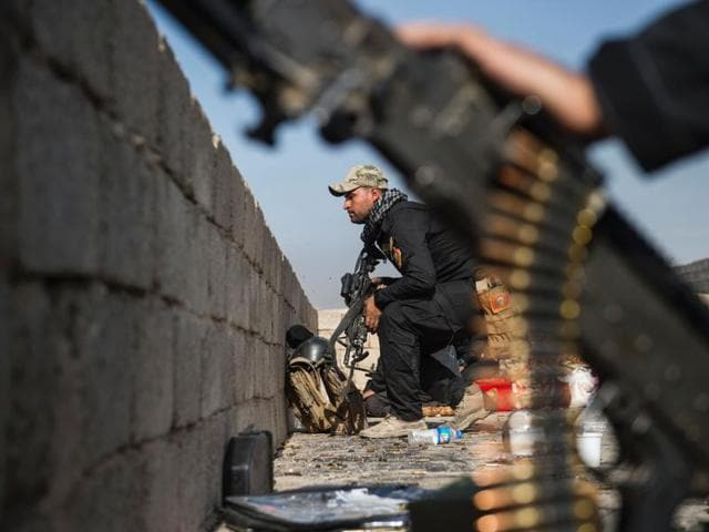 A soldier from the Iraqi Special Forces 2nd division crouches as he takes up a position while his comrades take cover behind a wall on a rooftop, in Mosul on Sunday.