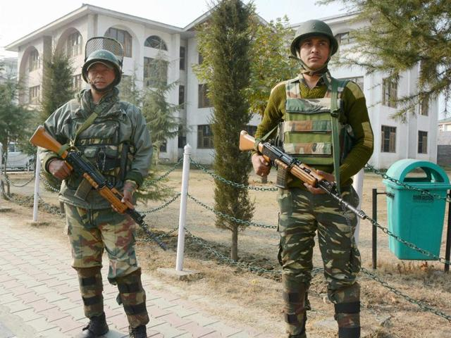 Security personnel stand guard at the head office of Jammu and Kashmir state board in Srinagar.