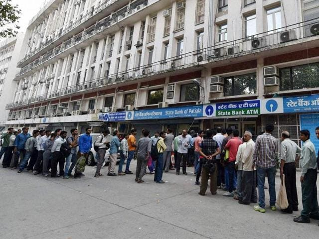 People stand outside an ATM to withdraw cash, in New Delhi.