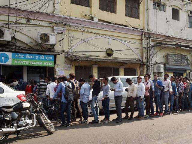 People stand in a long queue to collect cash from an ATM in Lucknow.