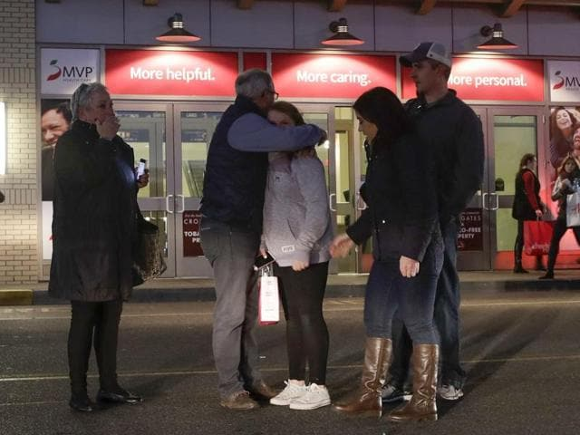 People embrace after leaving Crossgates Mall in Guilderland, New York after reports of gunfire inside on Saturday. The Albany Times-Union says hundreds of people were evacuated and the mall was locked down.