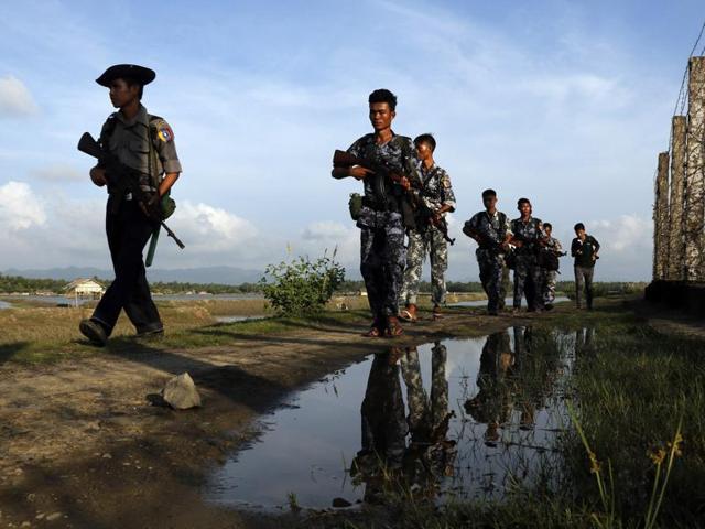 In this file photo, Myanmar police officers patrol along the border fence between Myanmar and Bangladesh in Maungdaw, Rakhine State, Myanmar.