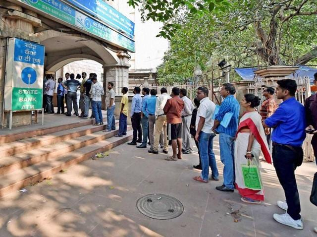 People queue outside a ATM to withdraw money in Siliguri on November 14, 2016.