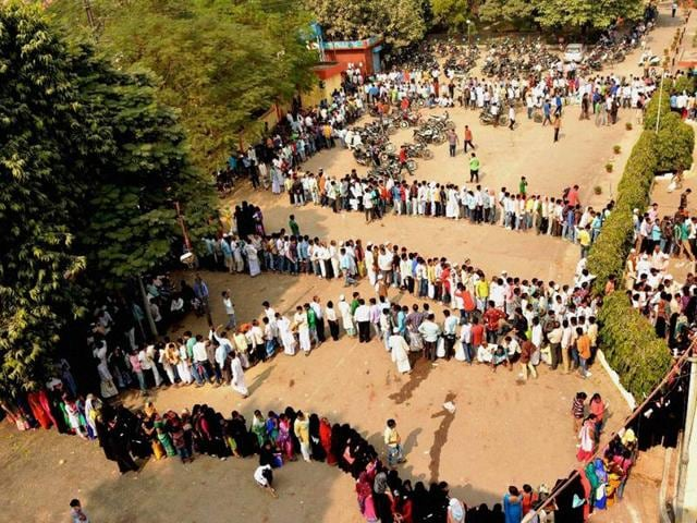 People queue up outside a bank to exchange their old Rs 500 and 1000 notes in Varanasi on Sunday.
