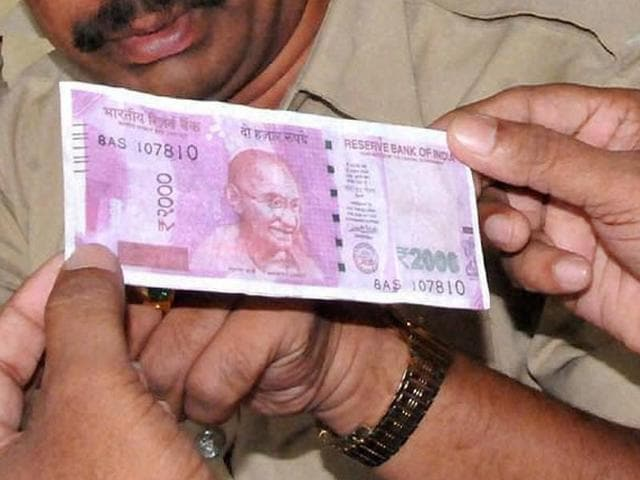 Police personnel inspect a photocopy of a Rs 2000-note, which was given to them by a vegetable seller.