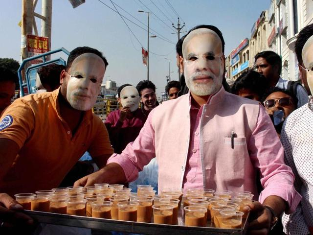 BJYM workers wearing masks of Prime Minister Narendra Modi serve tea to the people lined up outside banks and ATMs to get their old currency exchanged, in Bhopal on Tuesday.