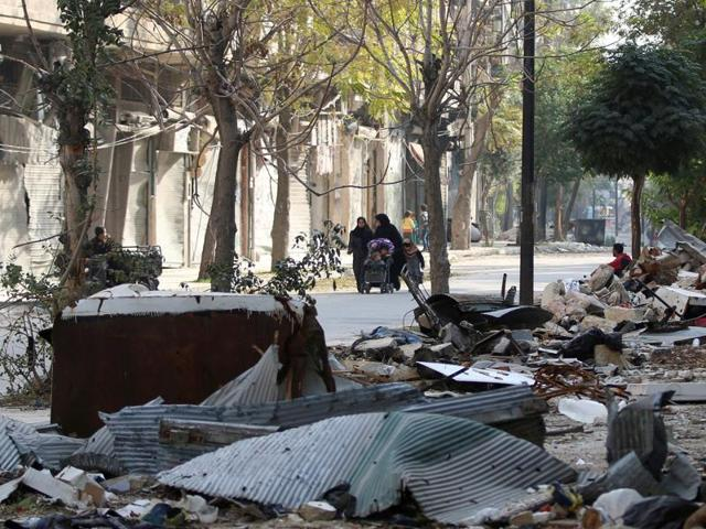 Civilians walk past debris of damaged buildings in the rebel held area of Old Aleppo, Syria on Monday.