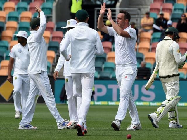 South Africa's Vernon Philander (L) watches as team captain Faf du Plessis shakes Australia's captain Steve Smith's hand after the match.