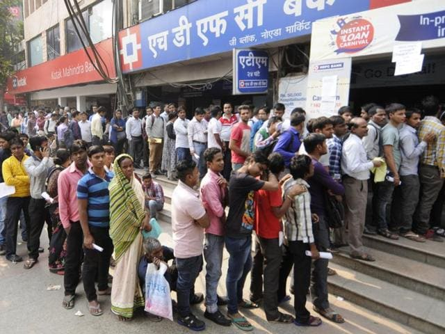 People wait in a long queue at a bank to deposit old denomination currency notes, in Noida.