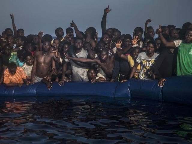 African refugees and migrants react aboard a partially punctured rubber boat as they wait to be assisted , during a rescue operation on the Mediterranean Sea on Sept 10.