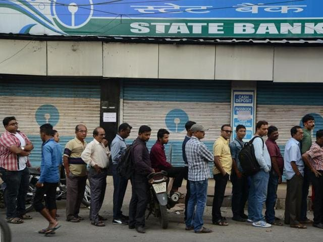 Customers queue up outside an ATM to withdraw money in Siliguri.