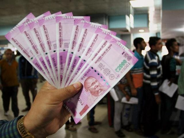 A man shows new Rs 2000 notes at a bank in Jammu.