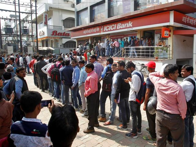 People queue outside a bank to exchange and deposit their old high denomination banknotes in Allahabad.