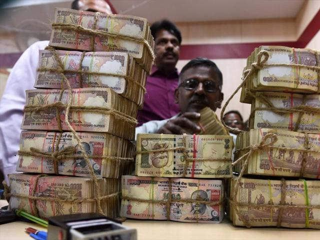 A bank employee counting bundles of Rs 1000 and Rs 500 notes at a cash counter in a Punjab National Bank branch in Chennai.