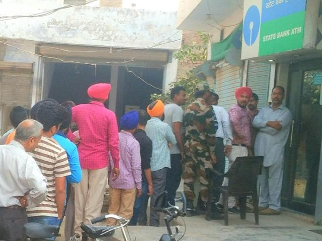 Poeple waiting outside an ATM in Patiala on Tuesday.