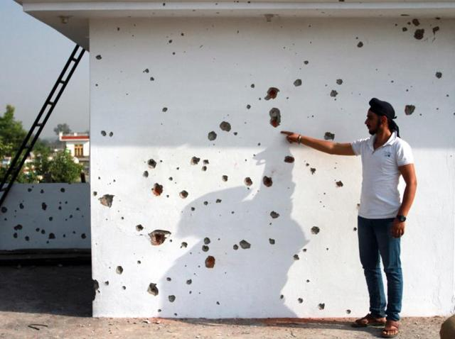 A civilian showing mortar shell marks on a wall after alleged firing from the Pakistan side of the border, at a residential area in Jammu and Kashmir.