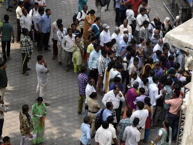 People queue up outside a bank branch at Sion on Wednesday.