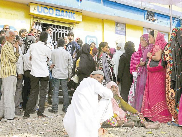 People stand outside an ATM in Jaipur on Wednesday.
