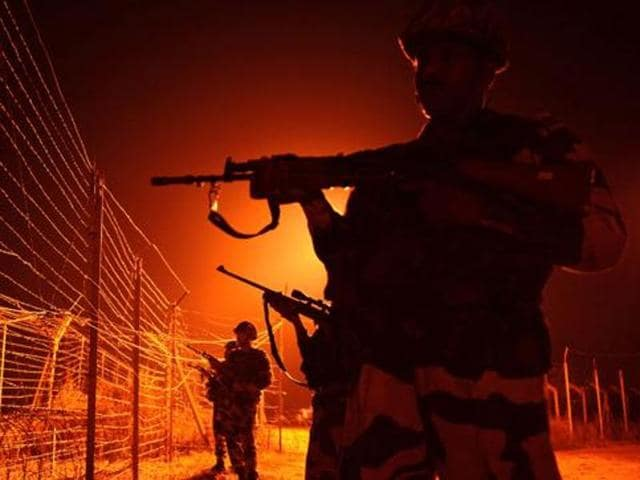 Indian Border Security Force (BSF) soldiers patrol along a border fence at an outpost along the Line of Control near Jammu.